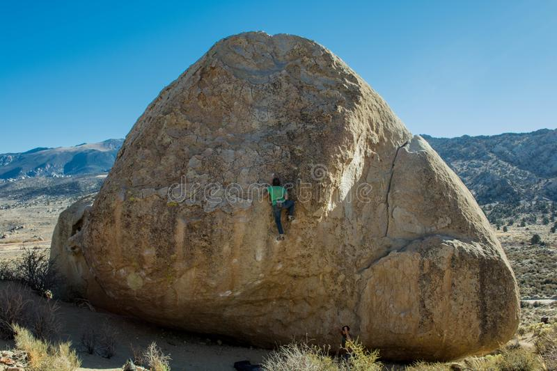 Man Rock Climbing a Large Boulder with Mountains in Background stock photo
