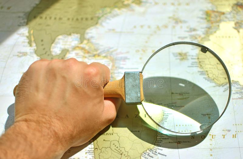 Strong man`s hand of a sailor with a magnifying glass on a world map stock photo