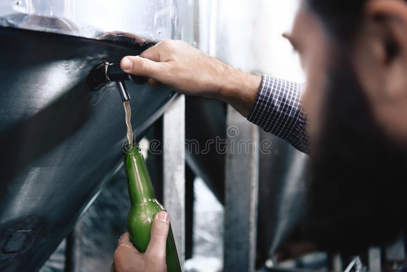 Strong man`s hands pour beer in bottle from beer tap at craft brewery. stock photos