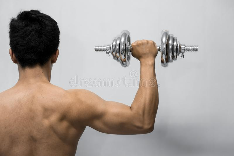 Strong man working out with dumbbell. Hand holding chrome dumbbell isolated on grey background stock image