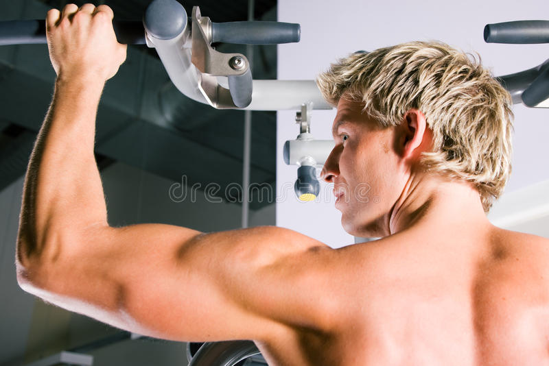 Strong man working out in gym stock images