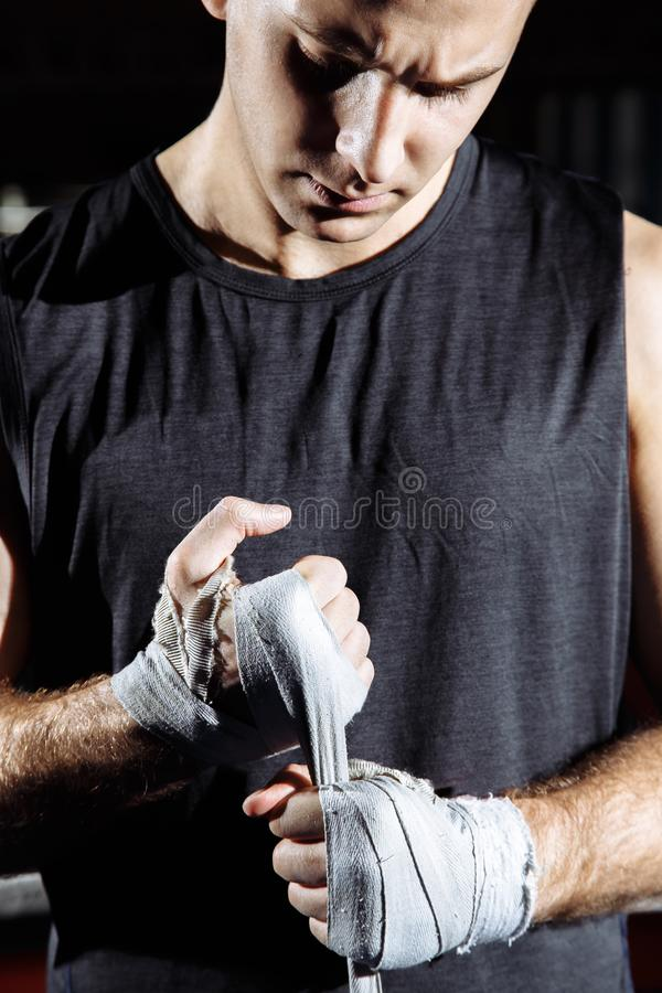 Strong man is wrapping hands with boxing wraps for fight and active exercise in fitness gym. royalty free stock photo