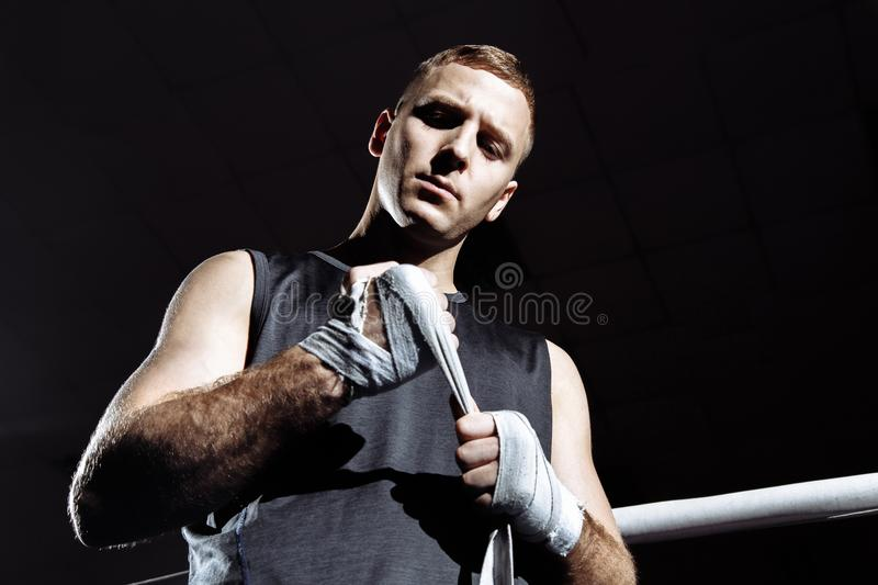 Strong man is wrapping hands with boxing wraps for fight and active exercise in fitness gym.  royalty free stock photography