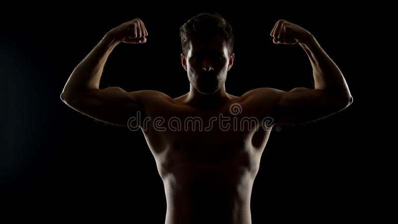 Strong masculine man showing biceps muscles, bodybuilding challenge, sports royalty free stock photography