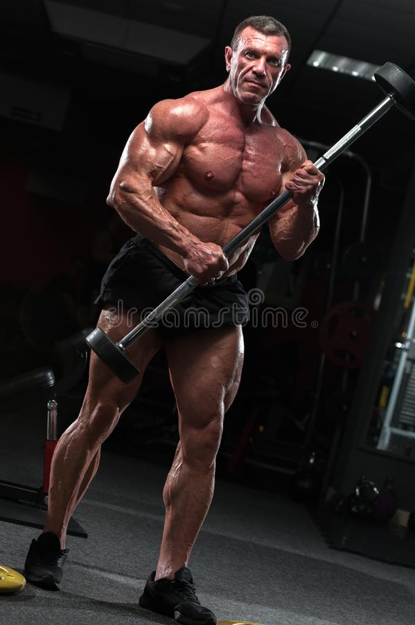 Strong mature man with relief body posing in gym royalty free stock photos