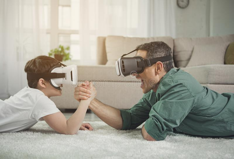 Excited father and son lying on floor and arm-wrestling. Strong men and boy competing in arm wrestling while wearing virtual reality goggles. They are situating royalty free stock images