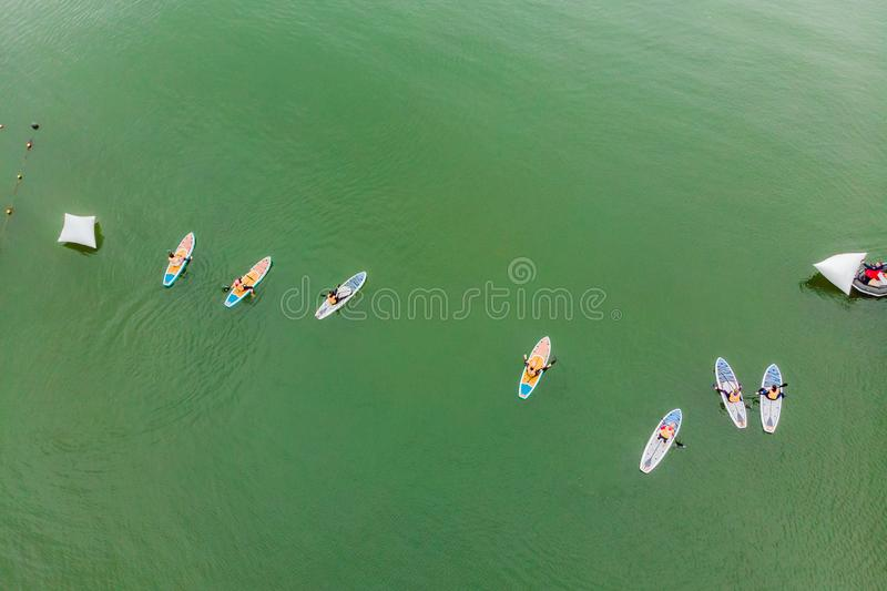 Strong men floating on a SUP boards in a beautiful bay on a sunny day. Aerial view of the men crosses the bay using the. Paddleboard. Water sports, competitions royalty free stock photo