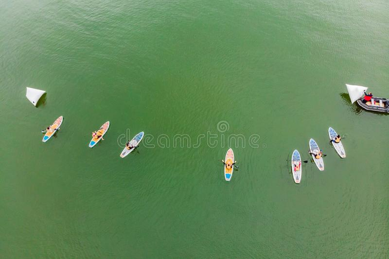 Strong men floating on a SUP boards in a beautiful bay on a sunny day. Aerial view of the men crosses the bay using the. Paddleboard. Water sports, competitions stock images