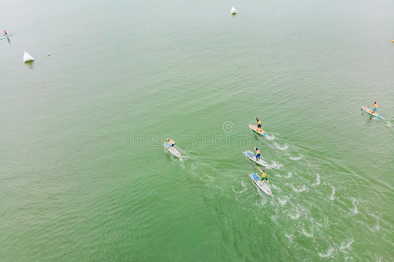 Strong men floating on a SUP boards in a beautiful bay on a sunny day. Aerial view of the men crosses the bay using the. Paddleboard. Water sports, competitions royalty free stock images