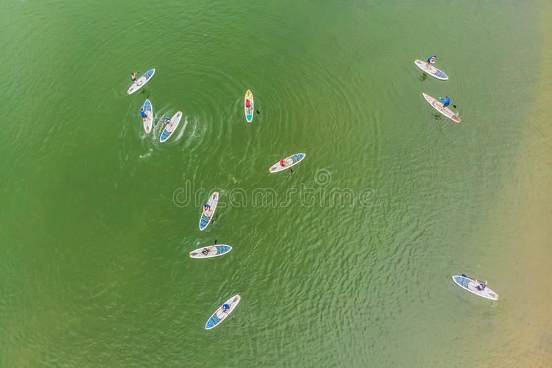 Strong men floating on a SUP boards in a beautiful bay on a sunny day. Aerial view of the men crosses the bay using the. Paddleboard. Water sports, competitions royalty free stock photography