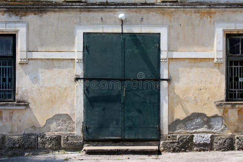 Strong metal doors locked and protected with metal bar surrounded with two windows with iron bars on each side of baroque style wa royalty free stock photos