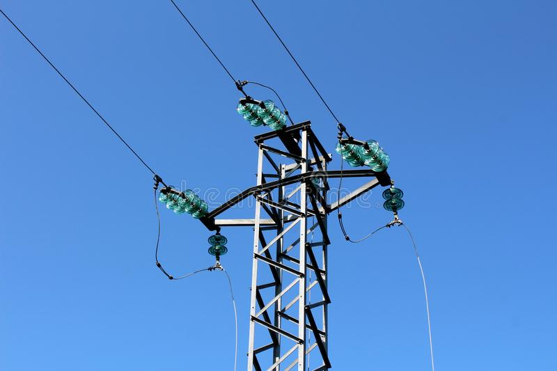 Strong metal power line connected with multiple wires and glass insulators on one side and cut wires on other surrounded with stock images