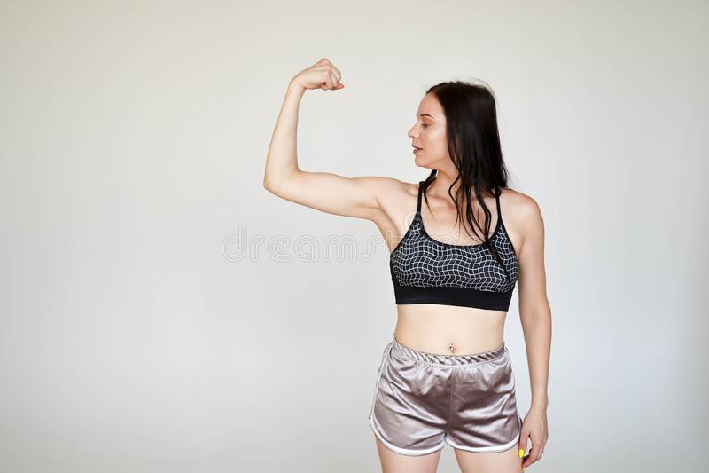 Strong model sporty slim lady wearing sports top and panties showing demonstrating arms muscules on white background with copy stock photography