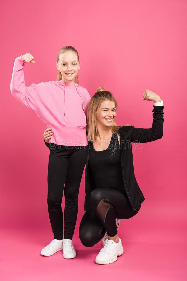 strong mother and daughter showing muscular biceps stock photography