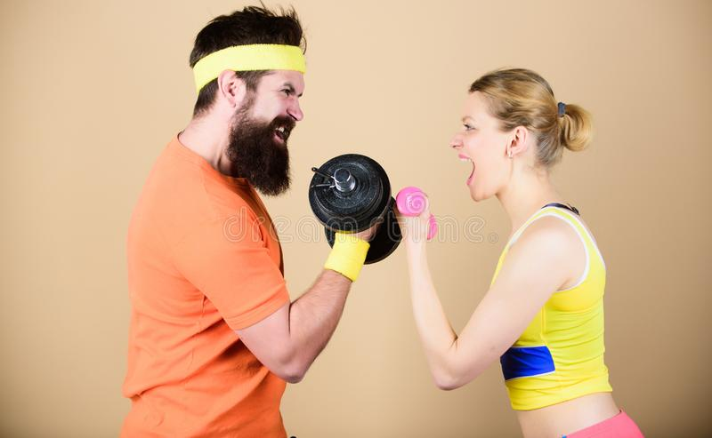 Strong muscles and power. Sporty couple training in gym. Athletic fitness competition. Weight lifting. Sport dumbbell. Equipment. Happy women and men workout stock images
