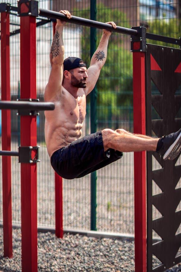 Strong Muscular bearded man doing abdominal exercise on horizontal bar in summer park. fitness, sport, exercising stock images