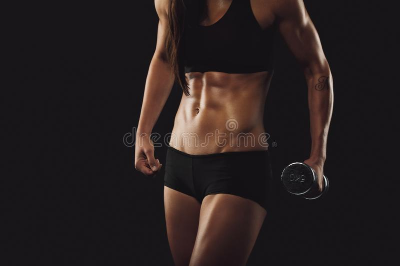 Strong and muscular build woman exercising with dumbbell royalty free stock photo