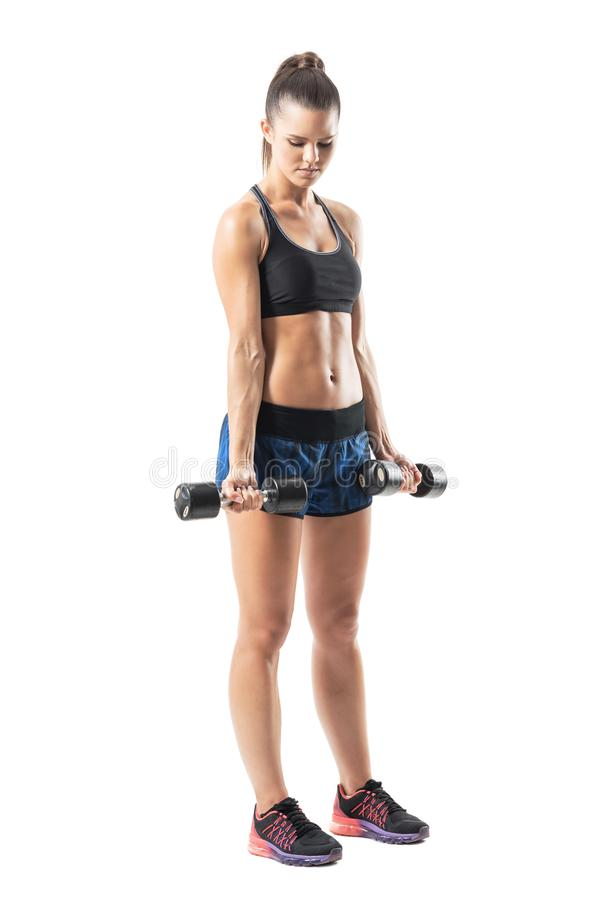 Strong muscular female athlete doing bicep dumbbell exercise in extended position. royalty free stock photography