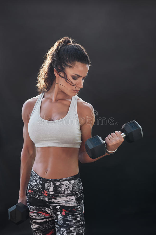 Strong and muscular female doing bodybuilding workout. With weights. Fitness woman exercising with dumbbells over black background stock photos