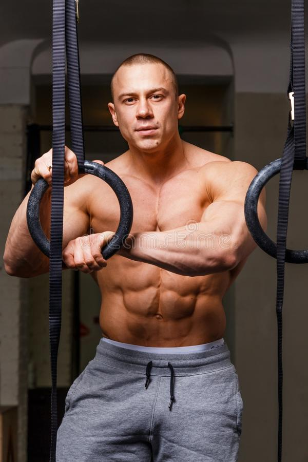 Strong muscular man. Bodybuilder poses and shows his abs stock images
