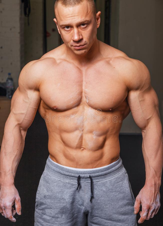 Strong muscular man. Bodybuilder poses and shows his body royalty free stock image