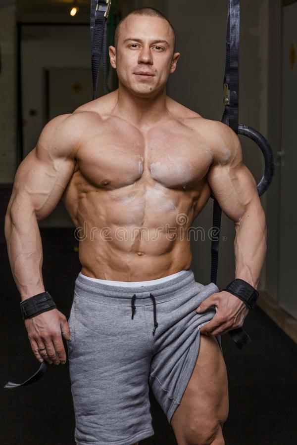 Strong muscular man. Bodybuilder poses and shows his body royalty free stock photo