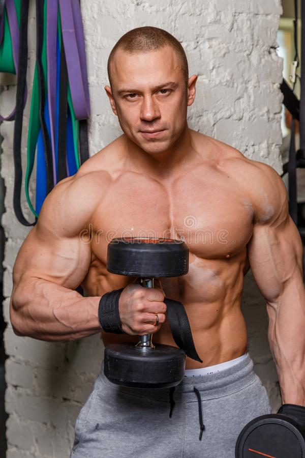 Strong muscular man. Bodybuilder shows his muscles holding dumbbells royalty free stock photo