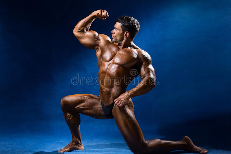 Strong muscular man bodybuilder shows his muscles royalty free stock image