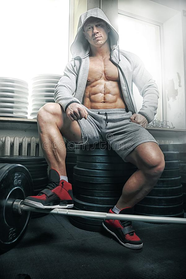 Strong muscular man. Bodybuilder sits on barbell plates stock images
