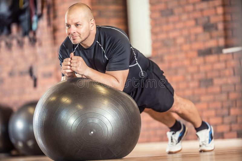 Strong muscular man exercising with fitness ball facilities in g. Ym or workout center royalty free stock image