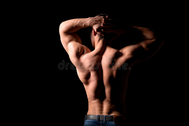 Strong muscular man holding his hands behind his head. Perfect shoulders and back muscles. Dramatic light stock images