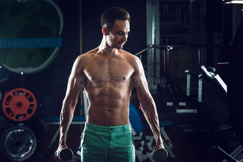 Strong Muscular man with naked torso abs working out in gym doing exercises with dumbell at biceps stock photos