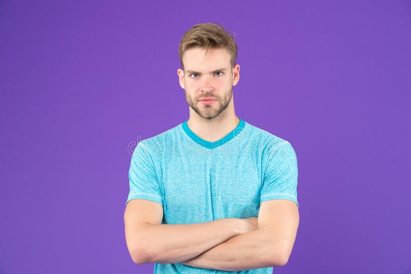 Strong and muscular. Man strict handsome unshaven guy on violet background. Masculinity concept. Man with muscular arms. Confident and strong. Does having stock image