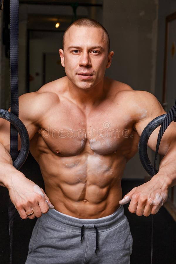 Strong muscular man. Bodybuilder poses and shows his abs royalty free stock images
