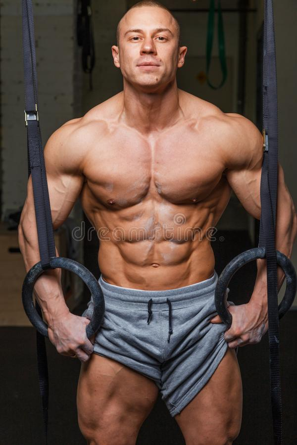 Strong muscular man. Bodybuilder poses and shows his body royalty free stock photography