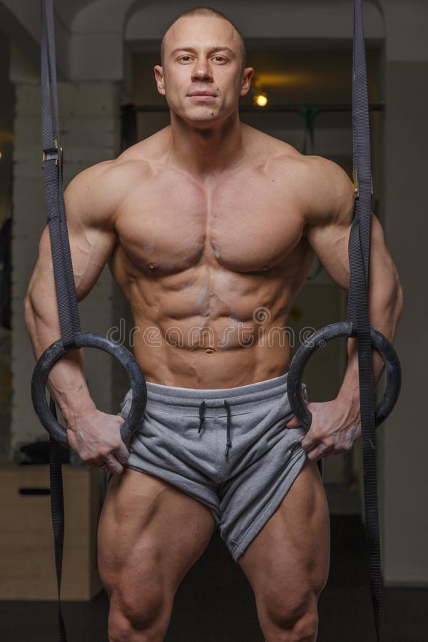 Strong muscular man. Bodybuilder poses and shows his body stock image
