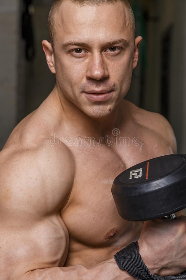 Strong muscular man. Bodybuilder shows his muscles holding dumbbell royalty free stock photos