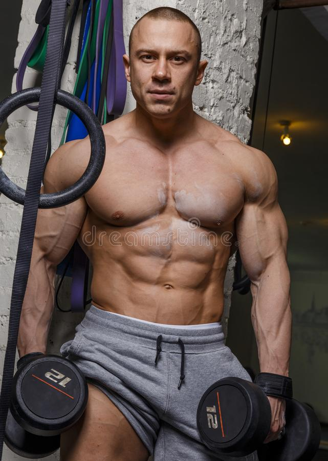 Strong muscular man. Bodybuilder shows his muscles holding dumbbells royalty free stock image
