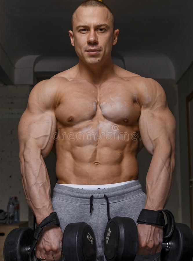 Strong muscular man. Bodybuilder shows his muscles holding dumbbells royalty free stock images