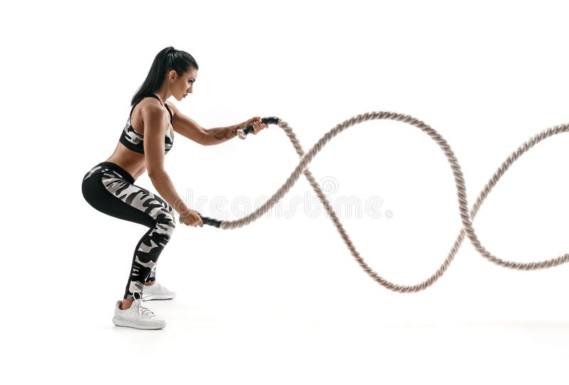 Strong muscular woman working out with battle ropes. stock photo