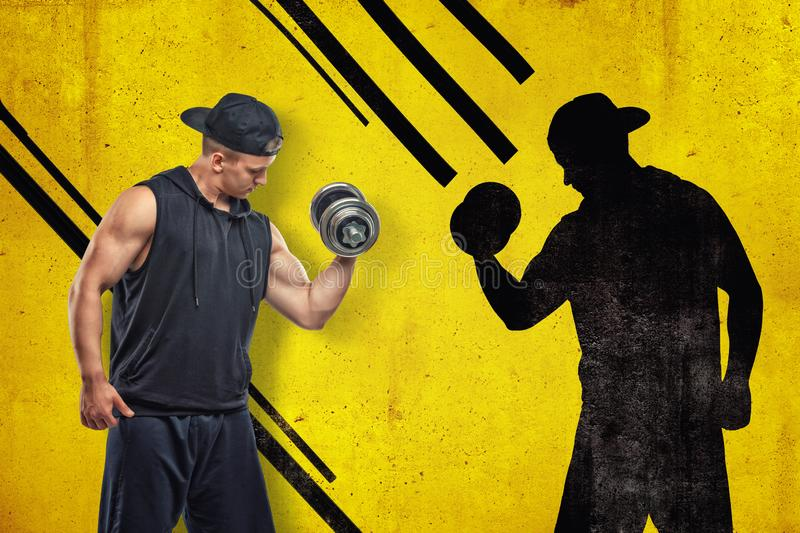 Strong muscular young man in black sportswear with a dumbbell with black shadow on yellow background royalty free stock photos