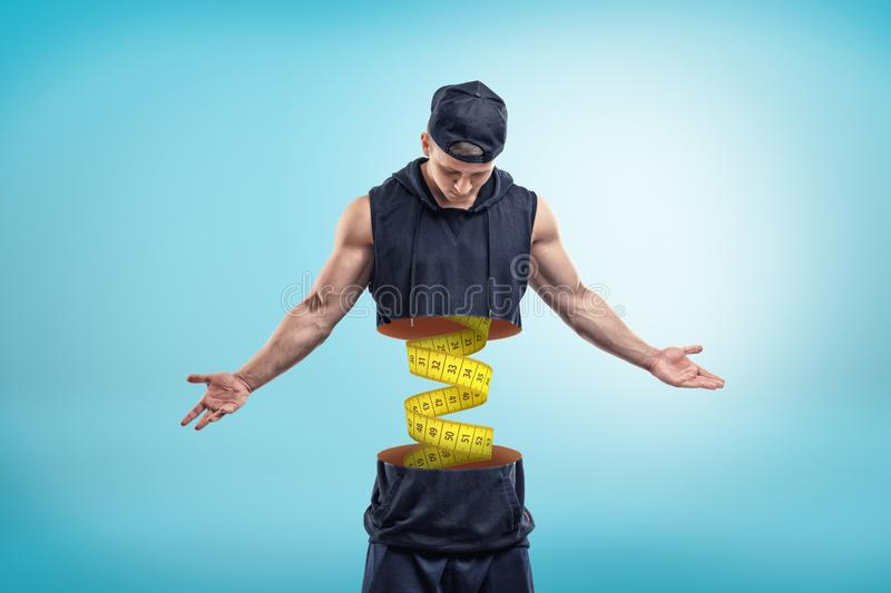 Strong muscular young man cut in half with yellow measuring tape inside on blue background stock illustration