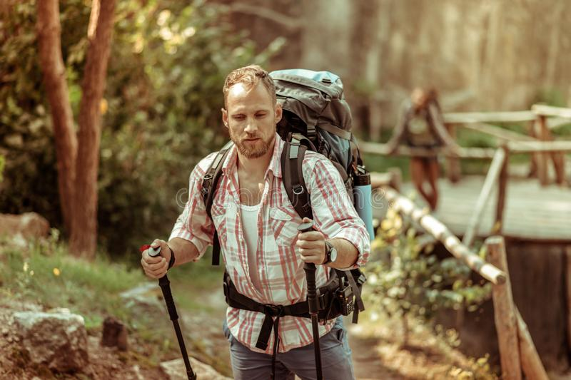 Strong nice young man carrying a backpack royalty free stock image