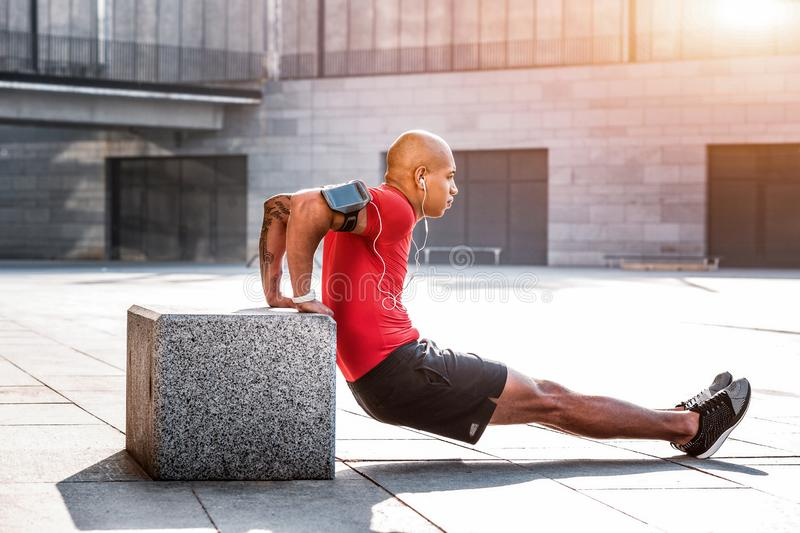 Strong nice young man developing his muscles. Sport is life. Strong nice man developing his muscles while doing sports activities stock photography