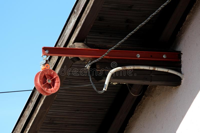 Strong plastic pulley mounted on metal pole on edge of family house roof next to electrical wires with clear blue sky in. Background on warm sunny spring day stock image