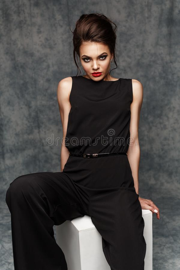 Strong and powerful business woman with red lips wearing black smart jumpsuit is posing on the cube in the studio. Success royalty free stock images