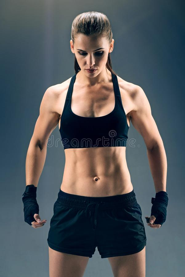 Strong powerful female boxer over dark background royalty free stock photography