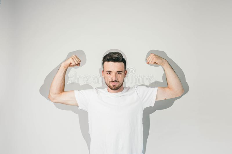 Strong and powerful guy is standing at white wall and posing to camera. He is showing his big muscles and how much royalty free stock image