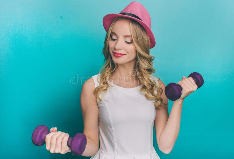 Strong and powerful teenager is doing some exercises. She is holding light dumbbels in her hands. She is looking at one stock photos