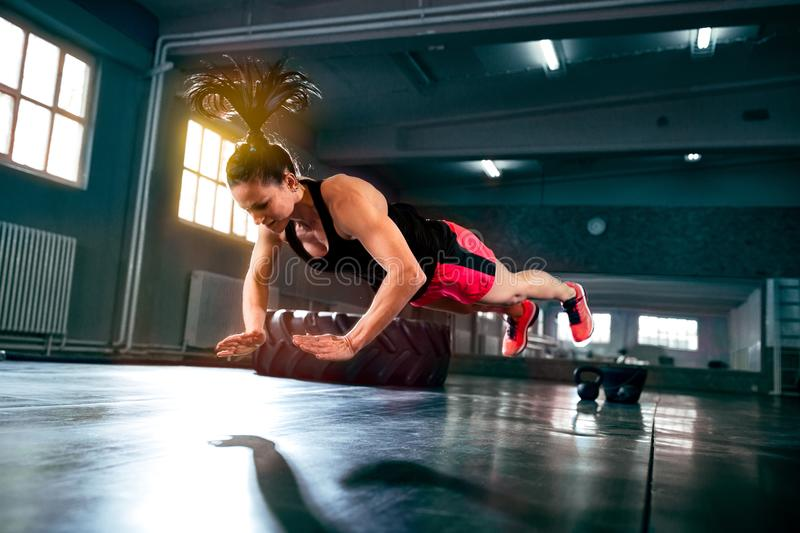 Strong powerful woman doing hard intense workout at gym. Flying push ups stock photo